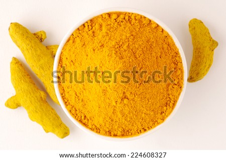 ground turmeric in ceramic bowl,Bowl of turmeric powder with  turmeric root - stock photo
