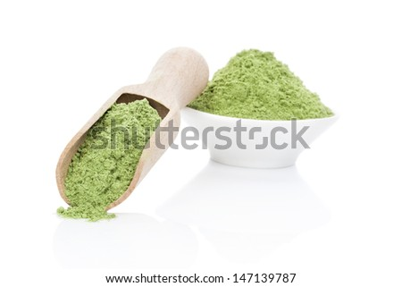 Ground wheat grass powder on wooden scoop and in bowl isolated on white background. Healthy lifestyle. Green food supplement. - stock photo