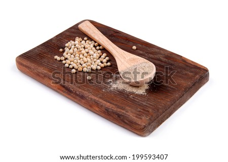 Ground white pepper and white pepper on a wooden board - stock photo
