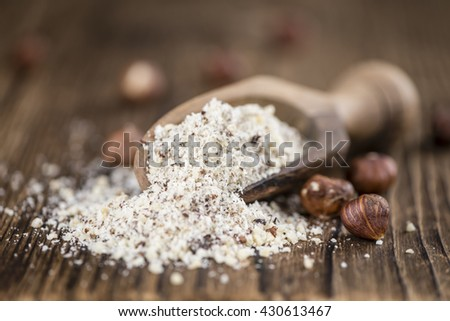Grounded Hazelnuts (selective focus; close-up shot) on vintage background - stock photo