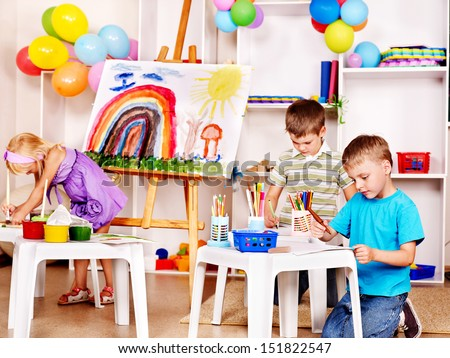 Group child painting at easel in school. - stock photo