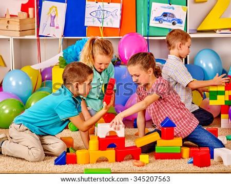 Group children build blocks on floor in kindergarten .  - stock photo