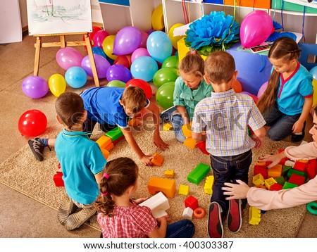 Group children game blocks on floor in kindergarten . Balloons on floor Top view. - stock photo