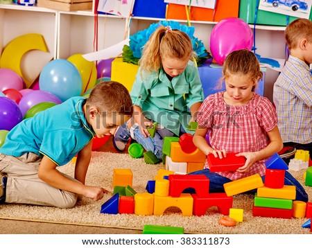 Group children game blocks on floor together in kindergarten . Top view. - stock photo