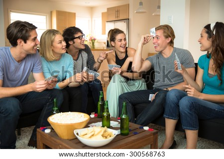 Group crowd of people friends at home in dorm playing games cards poker excited - stock photo