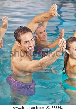 Group doing back training in water in hydrotherapy class in a swimming pool - stock photo