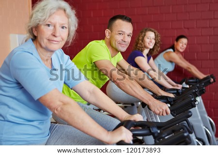 Group doing fitness training with spinning bikes in a health club - stock photo