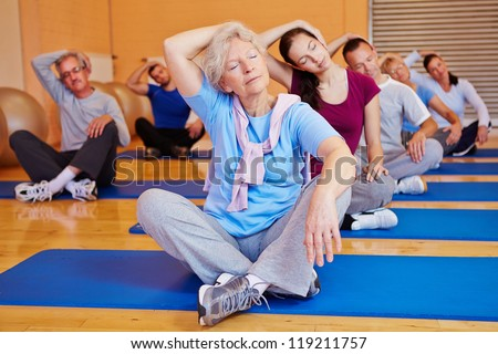 Group doing stretching exercises in back training class in a fitness center - stock photo