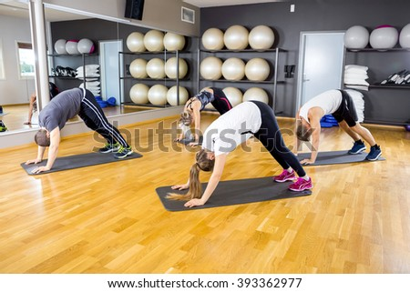 Group exercising body flexibility and balance at fitness gym - stock photo