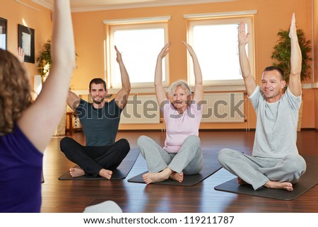 Group exercising cross-legged with fitness trainer in a health club - stock photo