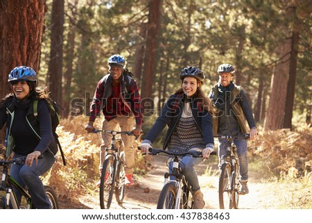 Group friends in helmets riding bikes in a forest, close up - stock photo