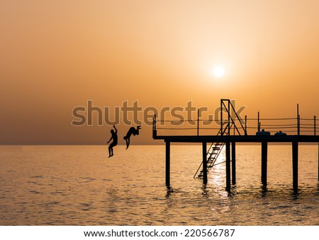 group happy of young boy jumping into the sea  - stock photo
