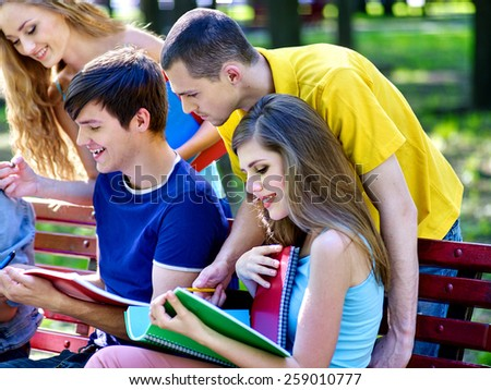 Group happy student with notebook on bench outdoor. Male and female. - stock photo