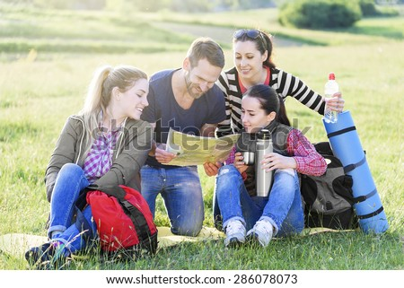 Group hikers on the grass with backpack watching the map, summer outdoor.  - stock photo
