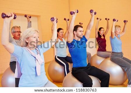Group in fitness center doing dumbbell training sitting on gym balls - stock photo