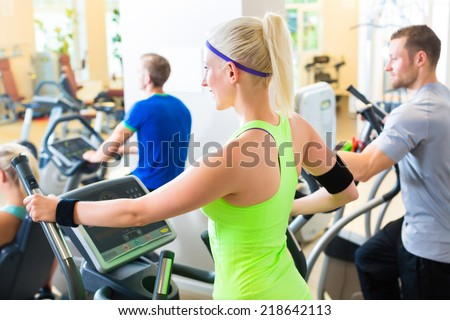 Group in gym on elliptical trainer - stock photo