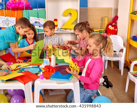 Group kids holding colored paper on table in kindergarten .Children learn together in kindergarten. - stock photo