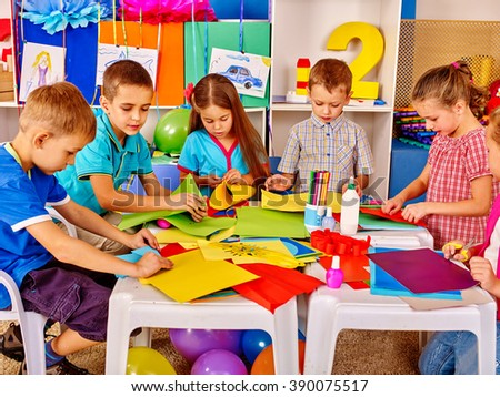 Group kids holding colored paper on table in kindergarten. Kids learning do origami. - stock photo