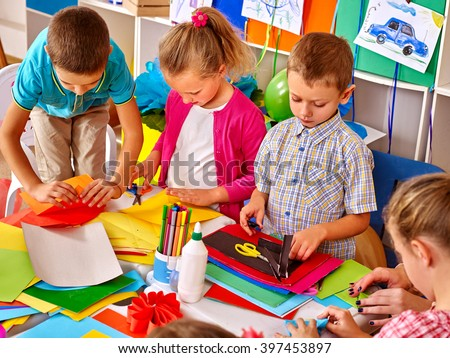 Group kids holding colored paper on table in preschooler. - stock photo