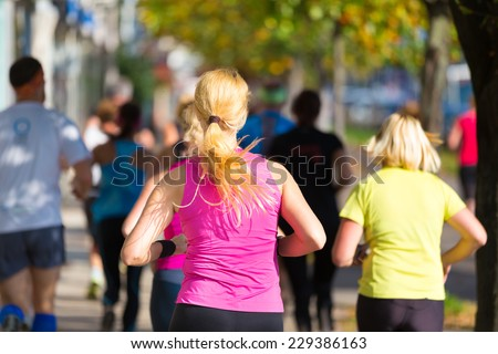 Group of active people running in the city. Healthy lifestyle. Weight Loss. Urban marathon run. - stock photo