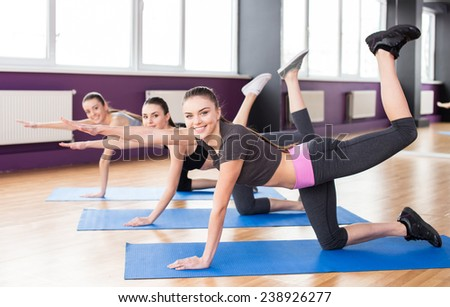 Group of active smiling women are training in fitness club. Smiling and looking at the camera. - stock photo