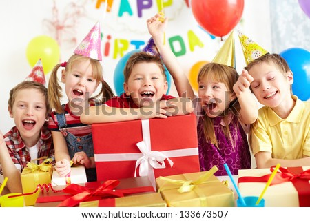 Group of adorable kids looking at camera with giftboxes near by - stock photo
