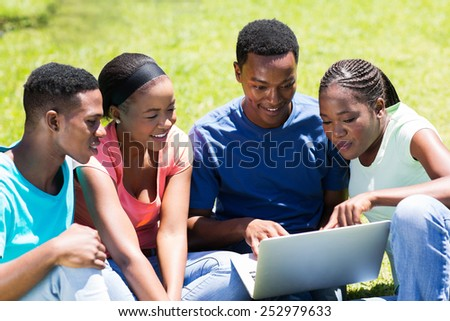 group of african university students using laptop outdoors - stock photo