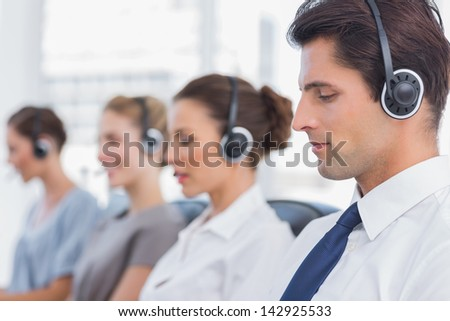 Group of agents sitting in line in a bright call centre - stock photo