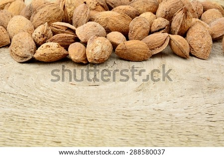 Group of almonds with shell on wooden plank - stock photo