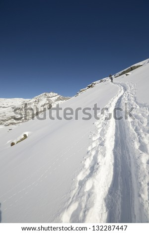 Group of alpinist hiking uphill by ski touring in powder snow with deep track in the foreground and scenic high mountain view in the background. Rear view. Polarizer effect in the sky. - stock photo