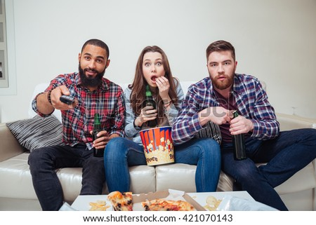 Group of amazed shocked young friends watching tv and eating popcorn on sofa - stock photo