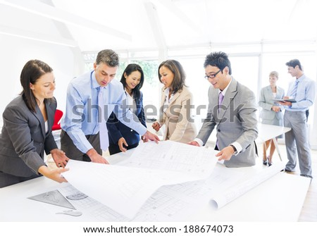 Group of Architects Planning on a New Project with their Blueprint - stock photo