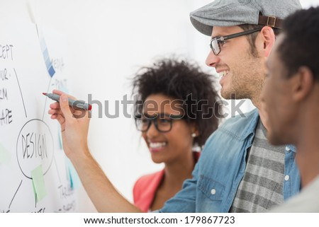 Group of artists in discussion in front of whiteboard at office - stock photo