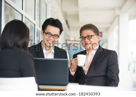 Group of  asian business people gathered together at a table discussing an interesting idea in the cafe - stock photo