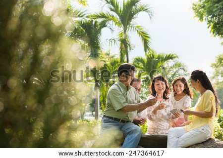 Group of Asian senior people playing cards outdoors - stock photo
