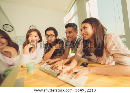 Group of Asian students watching educational video and doing outline - stock photo