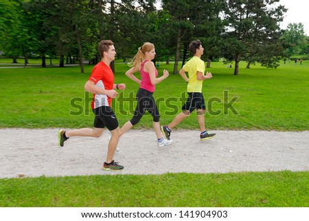 Group of athletes jogging in the park - stock photo
