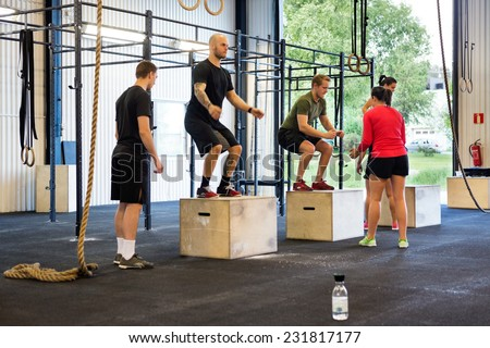 Group of athletes practicing box jumps at gym - stock photo