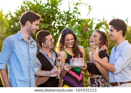 Group of attractive trendy young teenage friends toasting a birthday girl holding a cake with burning candles raising their flutes of champagne in congratulations - stock photo
