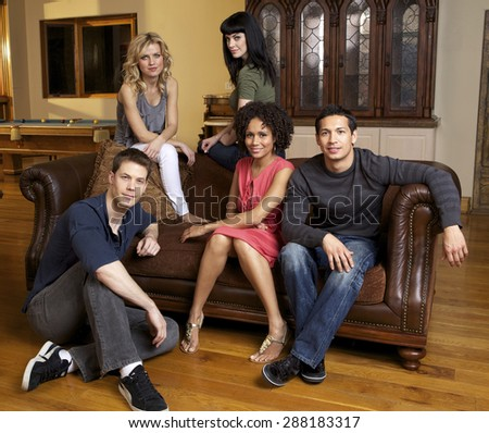Group of attractive young adults in a home posing around a sofa - stock photo