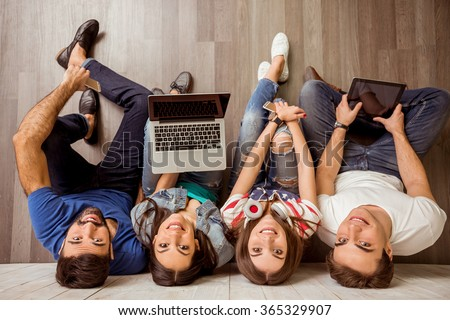 Group of attractive young people sitting on the floor using a laptop, Tablet PC, smart phones, headphones listening to music, smiling - stock photo