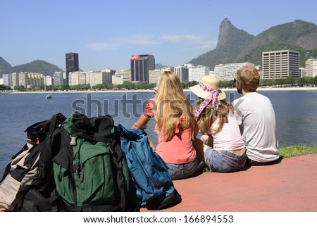 Group of backpackers tourists friends sitting on the edge of Guanabara bay watching the Christ the Redeemer. - stock photo