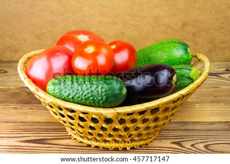 Group of backyard vegetables, tomato, cucumber, zucchini, eggplant in wicker basket on wooden background - stock photo
