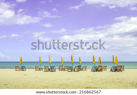 Group of beach chairs and closed umbrellas on white sand beach with cloudy blue sky. Concept for rest, relaxation and holiday in Thailand. - stock photo