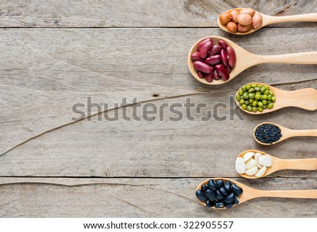 Group of beans and lentils in spoon made wood on wodden background. mung bean, groundnut, blackbean, black seasame, red kidney bean - stock photo