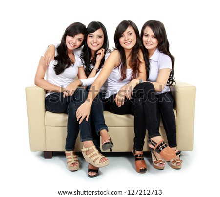 Group of beautiful asian women smiling together sitting on the couch isolated over white background - stock photo