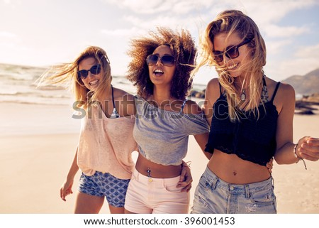 Group of beautiful young women strolling on a beach. Three friends walking on the beach and laughing on a summer day, enjoying vacation. - stock photo