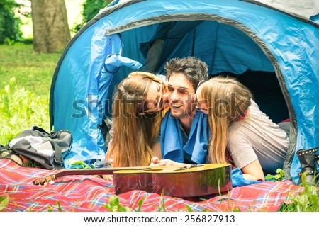 Group of best friends having fun camping together - Concept of carefree youth and freedom outdoors in the nature - Young people during vacations with lucky man flirting with beautiful girlfriends - stock photo