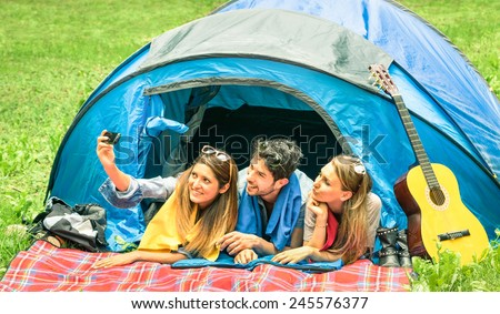 Group of best friends taking a selfie while camping together - Concept of carefree youth and freedom outdoors in the nature - Young people during vacations - stock photo