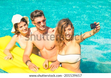 Group of best friends taking selfie at the swimming pool with yellow airbed - Concept of friendship in the summer with new trends and technology - Young man with girlfriends enjoying modern smartphone - stock photo